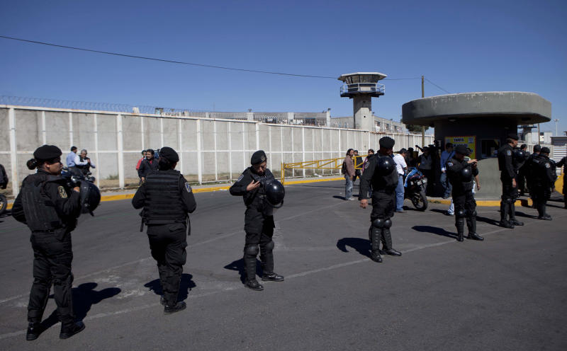 Police stand guard outside the prison where the head of Mexico's powerful teachers' union, Elba Esther Gordillo, is being held in Mexico City, Wednesday, Feb. 27, 2013. Mexico's most powerful woman was formally charged with a massive embezzlement scheme on Wednesday, standing grim-faced behind bars live on national television in what many called a clear message that the new government is asserting its authority. (AP Photo/Eduardo Verdugo)