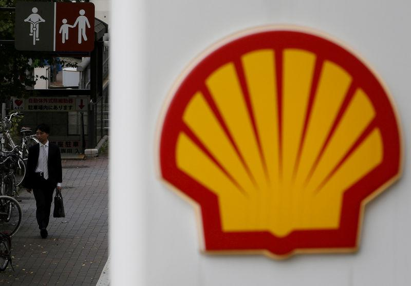 FILE PHOTO: A man walks behind a signboard of Showa Shell Sekiyu at its gas station in Tokyo