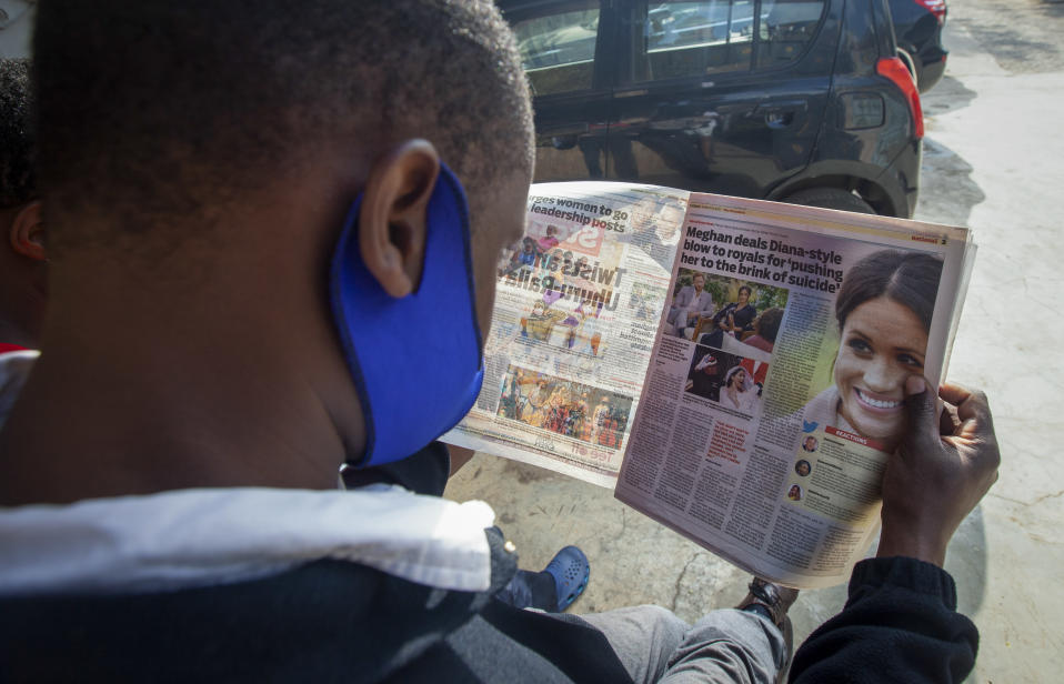 A man reads a copy of The Standard newspaper with coverage of the two-hour appearance of Britain's Prince Harry and Meghan with Oprah Winfrey, in Nairobi, Kenya Tuesday, March 9, 2021. Prince Harry and Meghan's explosive TV interview divided people around the world on Monday, rocking an institution that is struggling to modernize with claims of racism and callousness toward a woman struggling with suicidal thoughts. (AP Photo/Sayyid Abdul Azim)