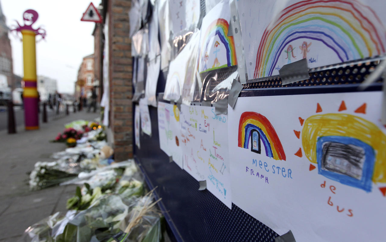 Flowers and tributes are placed outside the Sint Lambertus school in Heverlee, Belgium, to commemorate the pupils of the school involved in a bus crash in Switzerland, Wednesday, March 14, 2012. A tour bus slammed into a tunnel wall in the Swiss Alps on Wednesday morning in a horrific accident that killed 22 Belgian 12-year-old students returning from a joyous ski vacation as well as the six adults who were accompanying them. (AP Photo/Yves Logghe)