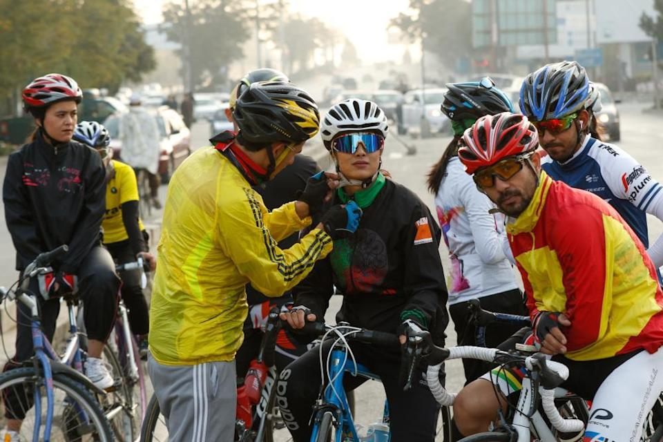 Ahmad Navid, a member of the Afghan national cycling team, helps Rukhsar Habibzai, the 22-year-old coach of the women's national cycling team, during their daily practice on the outskirts of Kabul, Afghanistan, in October 2020.