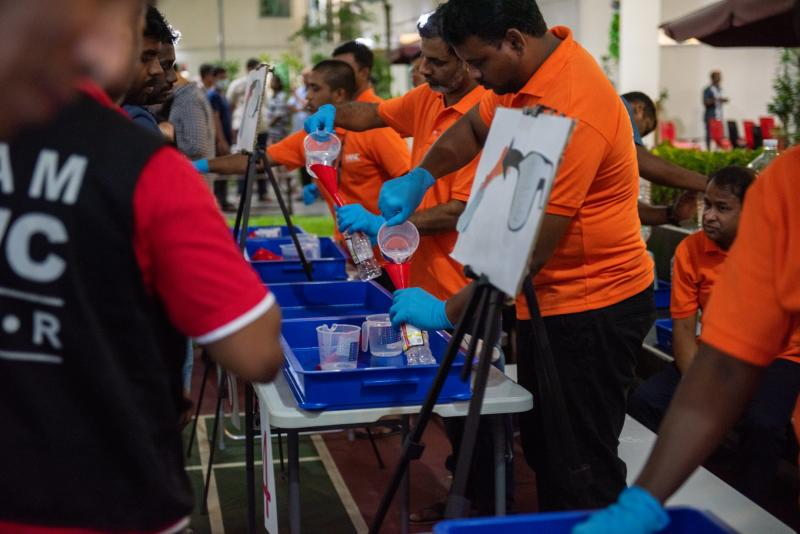 Filling stations are manned by volunteers at Migrant Workers' Centre. They work quickly to transfer the sanitisers into the recipient's clean, and labelled bottles. (PHOTO: Temasek)