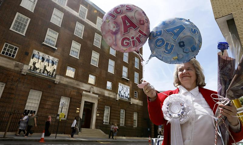 FILE - In this Monday, July 15, 2013 file photo royal supporter Margaret Tyler displays balloons for the media in front of the Lindo Wing at St Mary's Hospital in London. By the time you're reading this, the Duchess of Cambridge could be in labor. Or it could be a matter of hours. Or days. Or weeks. As Britain's Prince William and his wife, Kate, await the birth of their first child _ and the next heir to the English throne _ some are convinced the royal due date has already passed, even though the Palace has not given an exact date. Many in the British media predicted the baby would be born last week and the Prince himself is now on official leave. (AP Photo/Kirsty Wigglesworth, File)
