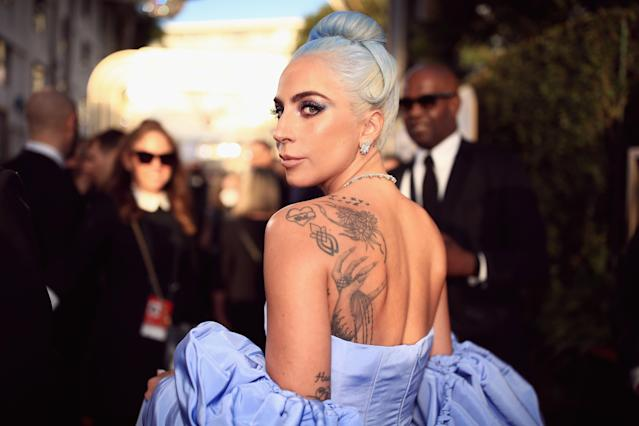 Lady Gaga chose to showcase her tattoos for the first time at the Golden Globes in a Valentino gown [Photo: Getty]