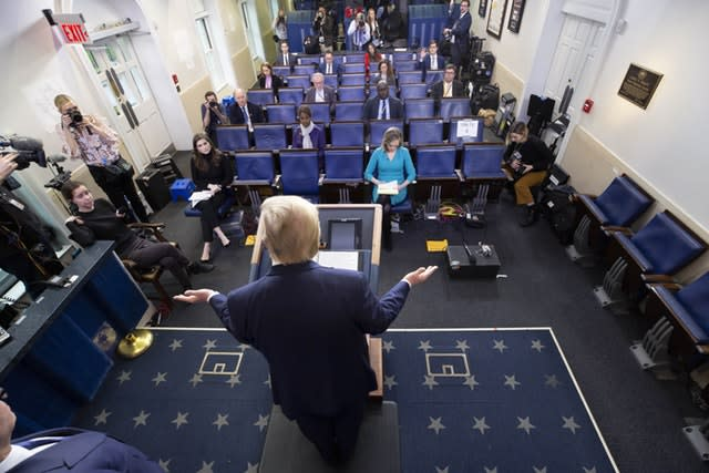 President Donald Trump gives his daily White House coronavirus briefing as reporters practise social distancing (Alex Brandon/AP)