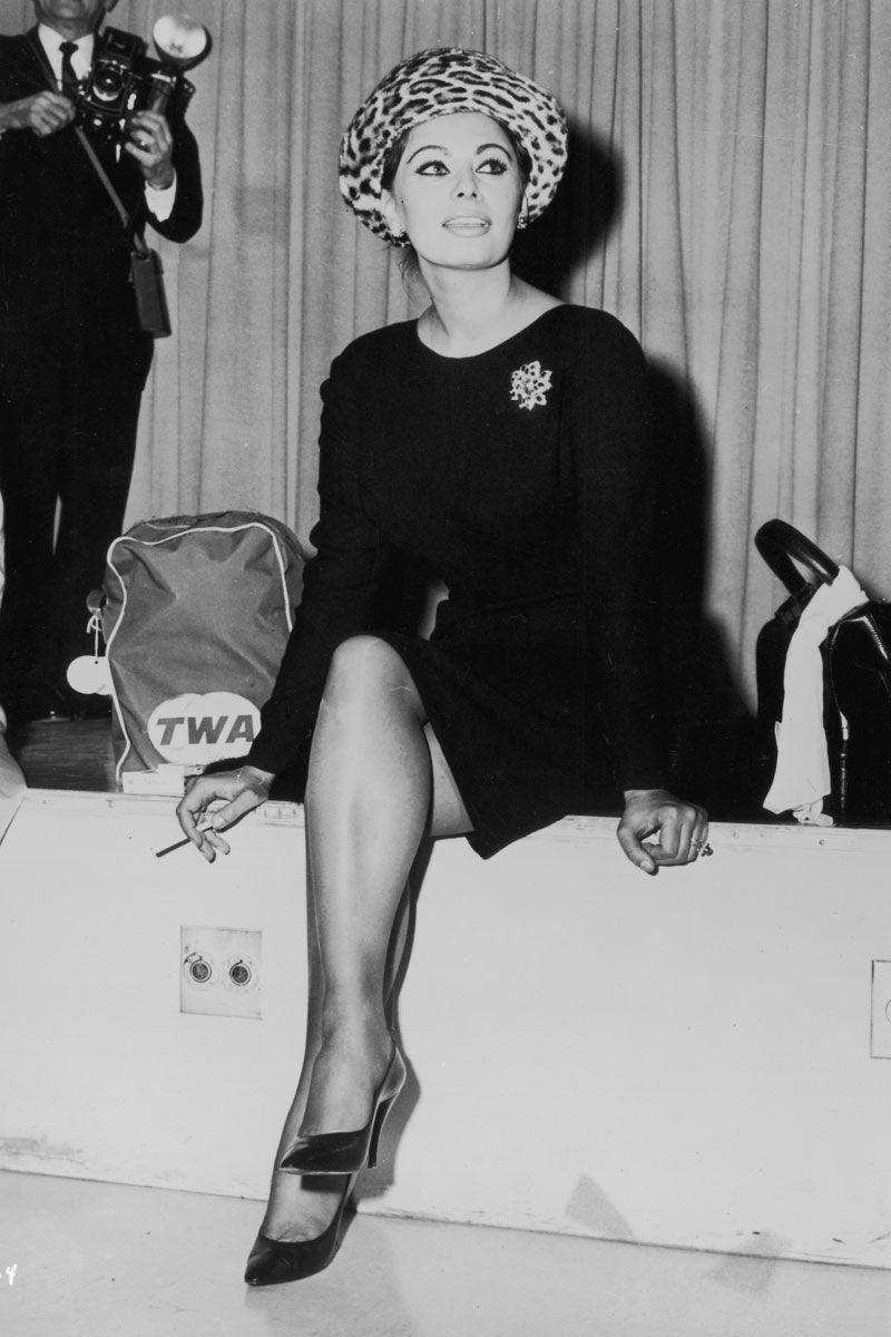 <p>Sophia Loren knew how to travel in style, which is why the actress opted for a belted black coat dress and cheetah print hat while flying with TWA in the '60s. </p>