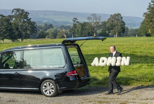 """Funeral director Tim Twigger from Full Circle Funerals, with a floral tribute that reads """"Admin"""", at Weston Church in Otley, West Yorkshire (Danny Lawson/PA)"""