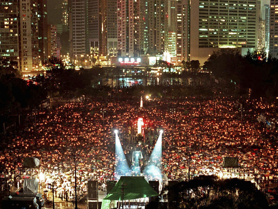 FILE - In this June 4, 1998, file photo, thousands of people held a candlelight vigil in the heavy rain at Victoria Park in Hong Kong to mark the ninth anniversary of the military crackdown in Tiananmen Square on a pro-democracy student movement in Beijing on the same day. The memorial is also the first time held under the Chinese rule since the British handover of Hong Kong in the previous year. (AP Photo/Vincent Yu, File)