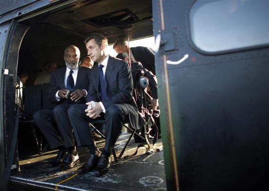France's President Nicolas Sarkozy (R) sits with Haitian President Rene Preval inside a helicopter before their flight over earthquake-hit areas in Port-au-Prince, February 17, 2010.