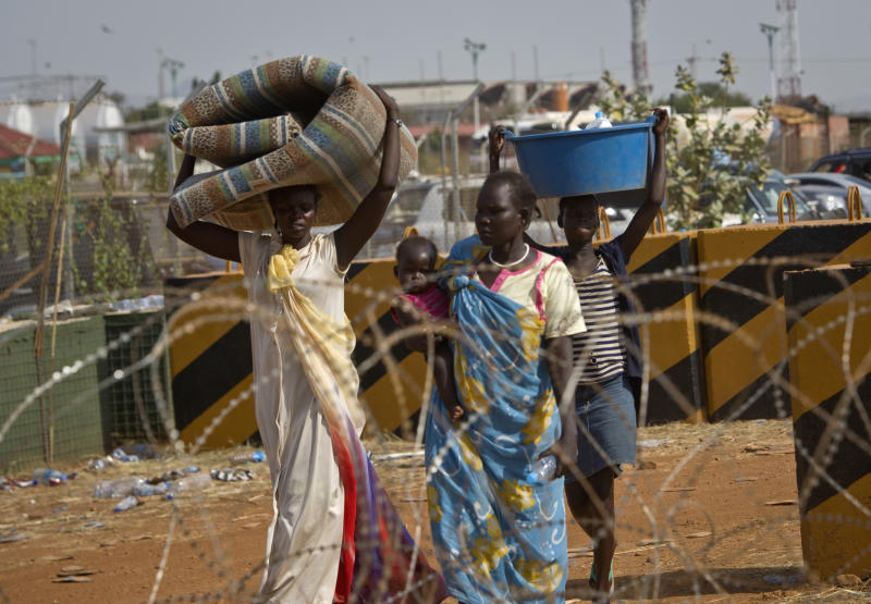 Displaced women carry belongings after seeking refuge at the compound of the United Nations Mission in South Sudan (UNMISS), in Juba, South Sudan Thursday, Dec. 19, 2013. South Sudan, the world's newest country, is threatened by rapidly escalating ethnic violence, as officials said Thursday that the government no longer controls the capital of its largest and most populous state. (AP Photo)