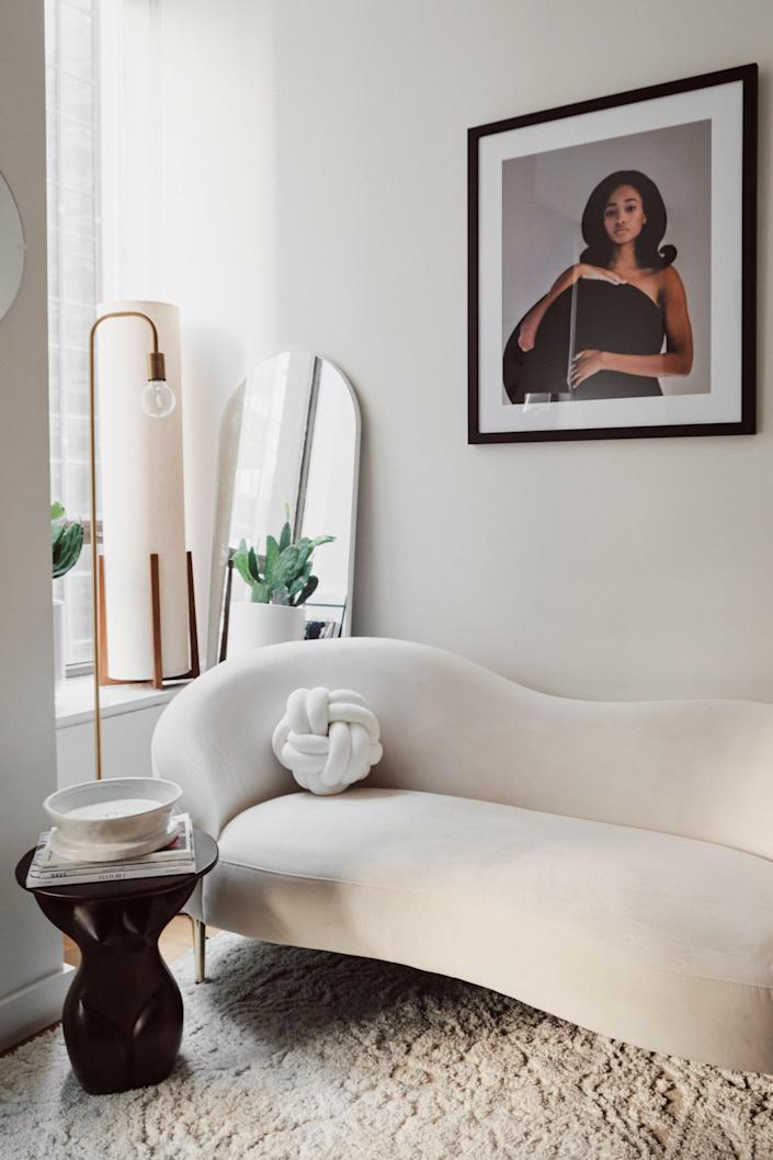 In the living room you'll find CB2's Curvo snow sofa, accessorized with a knot pillow from Etsy. The beacon brass floor lamp is from Article, and the framed shot above the sofa was taken by Christopher Tomas.