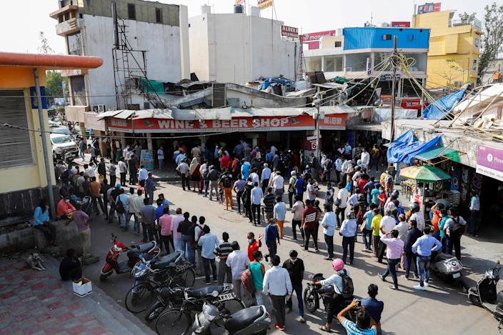 People line up outside a wine store to buy alcohol after Delhi's state government ordered a six-day lockdown to limit the spread of the coronavirus disease, in New Delhi, India, April 19, 2021. / Credit: ADNAN ABIDI/REUTERS