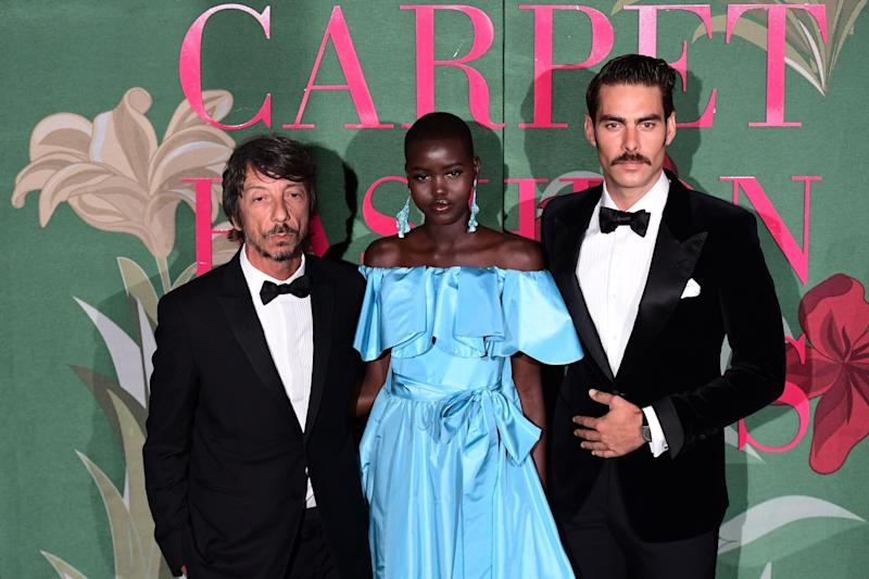 Italian fashion designer Pier Paolo Piccioli (L), South Sudanese model Adut Akech (C) and a guest arrive to attend the Green Carpet Fashion Awards