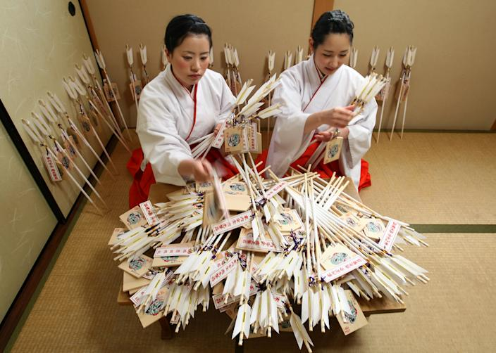 HIMEJI, JAPAN - DECEMBER 27: Mikos (shrine maidens) arrange 'Hamaya' (arrows intended to destroy evil spirits) to which 'Emas' (wooden plaques) are attached featuring a picture of dragon in celebration of the forthcoming 'Year of the Dragon' at Sosha Shrine on December 27, 2011 in Himeji, Japan. Japanese years are commonly associated with the twelve animals Mouse, Cow, Tiger, Rabbit, Dragon, Snake, Horse, Sheep, Monkey, Rooster, Dog and Pig. (Photo by Buddhika Weerasinghe/Getty Images)