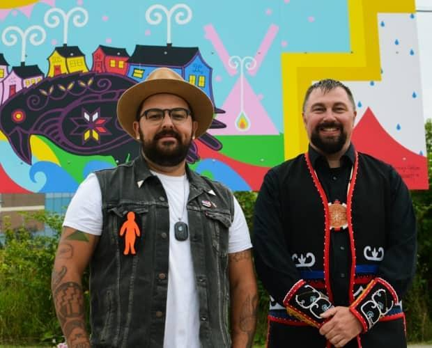 Jordan Bennett (left) and Marcus Gosse pose in front of their finished mural at its unveiling ceremony paying homage to the lost community of Crow Gulch. (James Grudić/CBC - image credit)