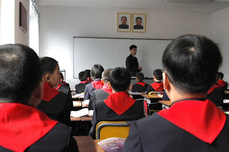 In this Monday, April 2, 2012 photo, North Korean pupils listen to their teacher standing under portraits of the late leaders of North Korea after the children took their seats during a ceremony to mark the start of a new school year at Pyongyang Middle School No. 1 in Pyongyang North Korea. (AP Photo/Jon Chol Jin)