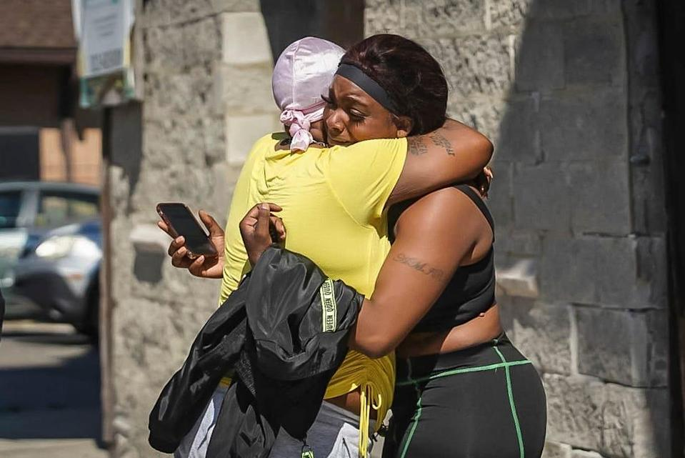 A woman receives a hug from a supporter outside the scene of a shooting outside a home in Chicago, Tuesday, June 15, 2021. Police say an argument at a house on Chicago's South Side erupted in fatal gunfire, leaving some dead and others injured.