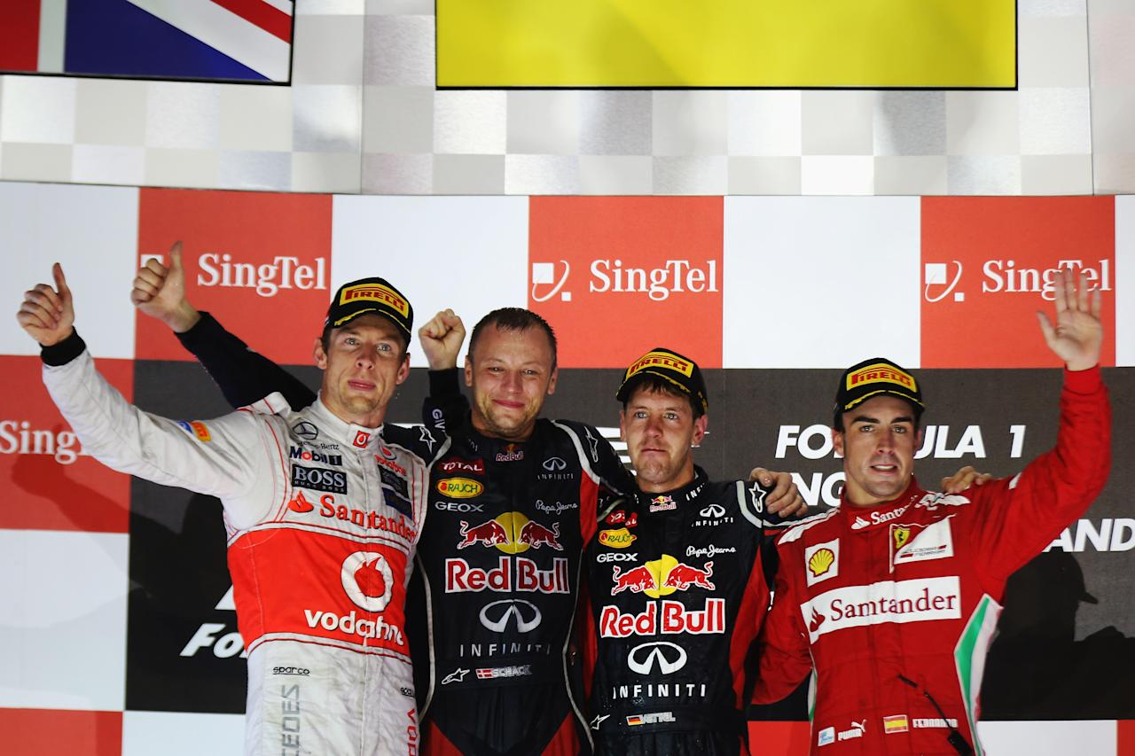 SINGAPORE - SEPTEMBER 23:  Race winner Sebastian Vettel (2nd right) of Germany and Red Bull Racing celebrates on the podium with second placed Jenson Button (left) of Great Britain and McLaren, third placed Fernando Alonso (right) of Spain and Ferrari and Ole Schack (2nd left) following the Singapore Formula One Grand Prix at the Marina Bay Street Circuit on September 23, 2012 in Singapore, Singapore.  (Photo by Mark Thompson/Getty Images)