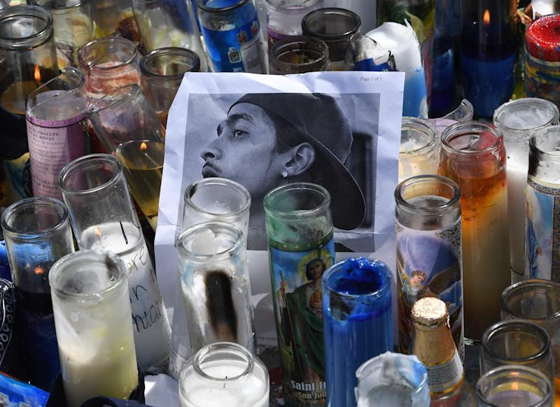 A photo and candles are displayed at a makeshift memorial outside The Marathon clothing store owned by Grammy-nominated rapper Nipsey Hussle where he was fatally shot along with 2 other wounded in Los Angeles, California on April 1, 2019. - The Grammy-nominated rapper found minor commercial success but was highly revered among his peers, and his shock death triggered an outpouring of tributes from hip hop royalty. (Photo by Mark RALSTON / AFP)MARK RALSTON/AFP/Getty Images ORIG FILE ID: AFP_1FA8DH
