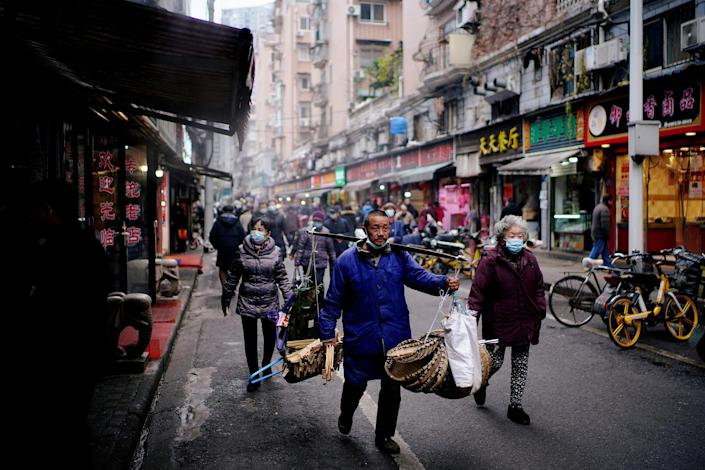 Image: People wearing protective masks walk at a street market almost a year after the start of the coronavirus disease (COVID-19) outbreak, in Wuhan, Hubei province (Aly Song / Reuters)