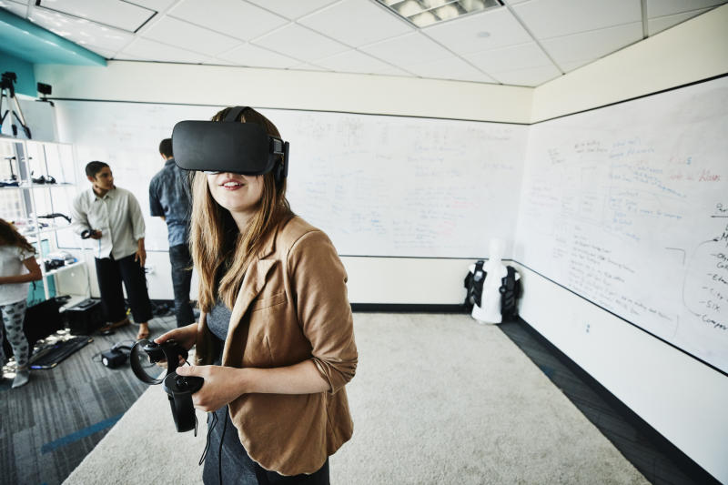 Female engineer using virtual reality headset in computer lab