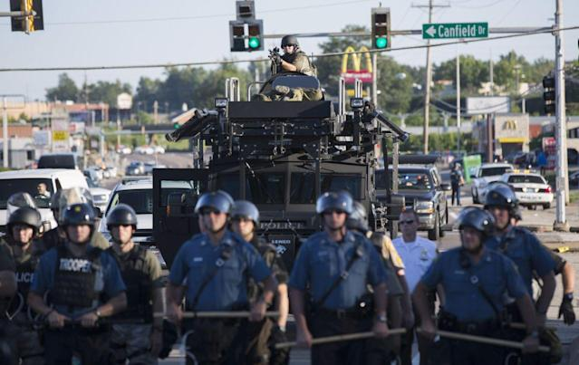 <p>Riot police stand guard as demonstrators protest the shooting death of teenager Michael Brown in Ferguson, Missouri August 13, 2014. Police in Ferguson fired several rounds of tear gas to disperse protesters late on Wednesday, on the fourth night of demonstrations over the fatal shooting of an unarmed black teenager Brown, 18, by a police officer on August 9 after what police said was a struggle with a gun in a police car. A witness in the case told local media that Brown had raised his arms to police to show that he was unarmed before being killed. (Mario Anzuoni/Reuters) </p>