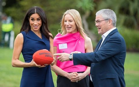 The Duchess of Sussex gets to grips with an Australian Rules football during a visit to Melbourne - Credit: Reuters