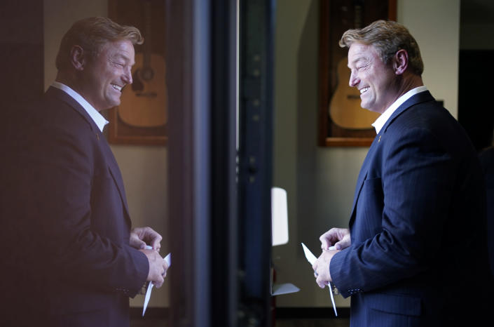 Former U.S. Sen. Dean Heller is reflected in a window at Share Village Las Vegas after announcing a bid for governor of Nevada, Monday, Sept. 20, 2021, in Las Vegas. (AP Photo/John Locher)
