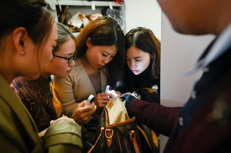 Trainees practice methods of verifying the authenticity of a handbag following a class at the Extraordinary Luxuries Business School in Beijing