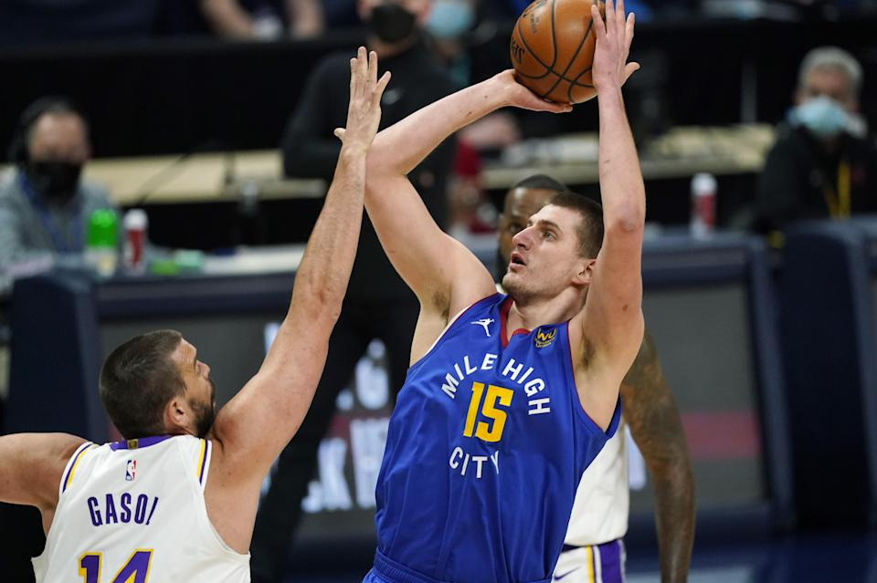Denver Nuggets center Nikola Jokic, right, goes up to shoot over Los Angeles Lakers center Marc Gasol in the first half of an NBA basketball game Sunday, Feb. 14, 2021, in Denver. (AP Photo/David Zalubowski)