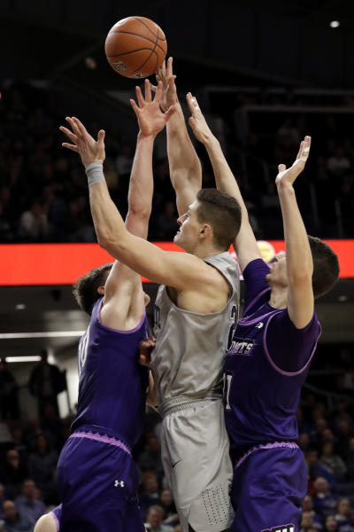 Penn State forward John Harrar, center, shoots against Northwestern forward Miller Kopp, left, and forward Robbie Beran during the first half of an NCAA college basketball game in Evanston, Ill., Saturday, March 7, 2020. (AP Photo/Nam Y. Huh)