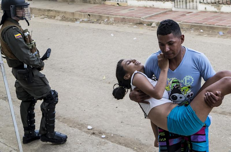 A teenage girl is brought to hospital in Carmen de Bolivar, Bolivar Province, Colombia, after fainting on September 3, 2014 (AFP Photo/Joaquin Sarmiento)