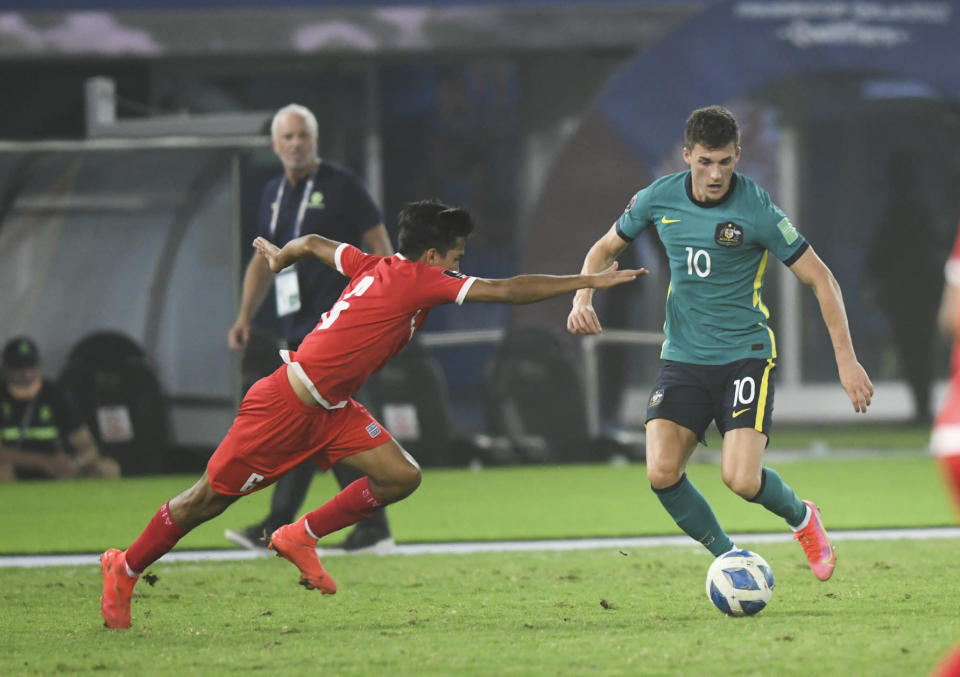 Australia's Ajdin Hrustic, right, and Nepal's Suman Aryal fight for the ball during the World Cup 2022 Group B qualifying soccer match between Nepal and Australia in Kuwait City, Kuwait, Friday. June 11, 2021. (AP Photo/Jaber Abdulkhaleg)