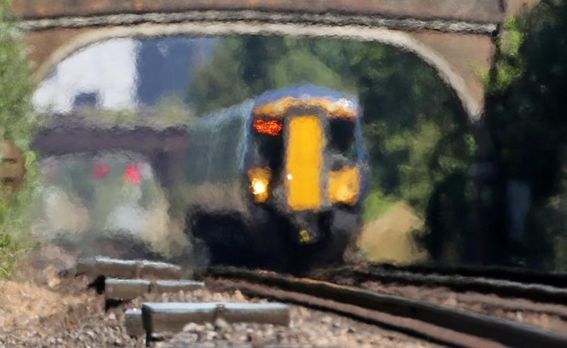 A train moves through heat haze in Ashford, Kent, as the continued hot weather causes problems across the rail network.