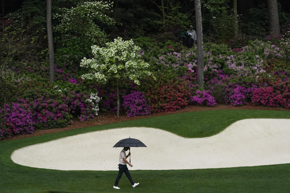 Justin Rose, of England, walks in the rain to the 13th green during the third round of the Masters golf tournament on Saturday, April 10, 2021, in Augusta, Ga. (AP Photo/Gregory Bull)