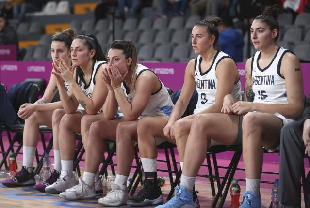 ADDS REASON WHY ARGENTINA IS OUT OF THE MEDAL ROUND - Argentina's players watch the women's basketball match against the Virgin Islands from the bench, at the Pan American Games in Lima, Peru, Thursday, Aug. 8, 2019. Argentina's women's basketball team had to forfeit its match against Colombia at the Pan American Games on Wednesday for wearing the wrong uniform color. Argentina won todays match against the Virgin Islands but is out of the medal rounds because of the uniform blunder. (AP Photo/Martin Mejia)