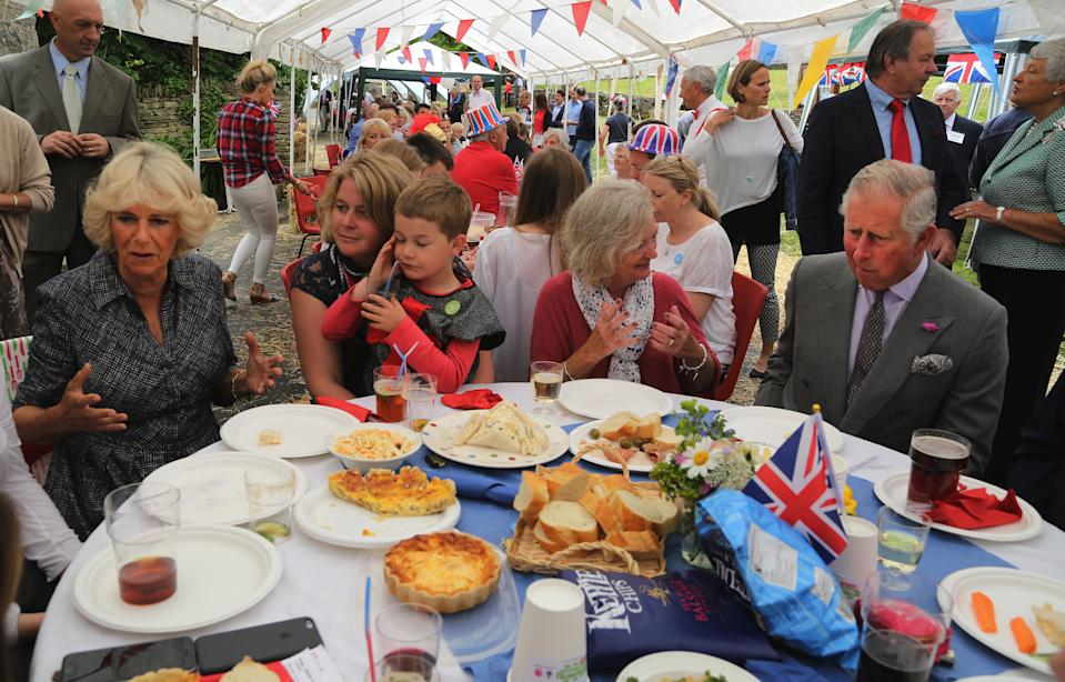 BRIMPSFIELD, ENGLAND - JUNE 12: Prince Charles, Prince of Wales (R) and Camilla, Duchess of Cornwall (L) attend a street party as part of the three day celebrations for Queen Elizabeth II's official 90th birthday on June 12, 2016 in Brimpsfield, Gloucestershire. The Big Lunch is an annual event started by the Eden Project which aims to get as many people as possible to have lunch together, in their neighbourhoods, in order to encourage more of a community spirit throughout the Nation. (Photo by Geoff Caddick - WPA Pool/Getty Images)
