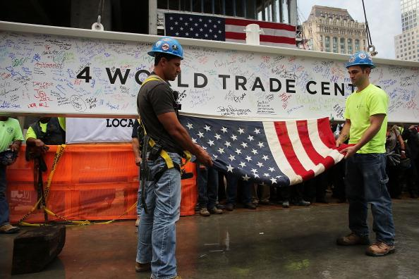 Construction workers Danny Conca (L) and Brian Shelly hold an American Flag attached to the last steel beam, signed by members of the crews that helped build the tower, as it is hoisted 977 feet to the top of Four World Trade Center on June 25, 2012 in New York City. The trapezoidal glass and steel office building, which is designed as an architectural backdrop to the September 11 Memorial, is scheduled to open in 2013. (Photo by Spencer Platt/Getty Images)