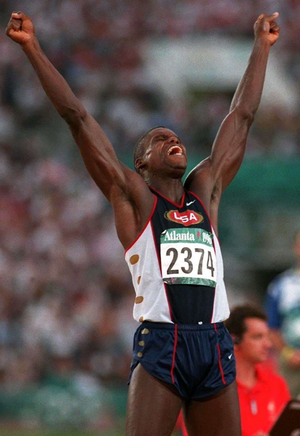 FILE - In this Monday, July 29, 1996, file photo, Carl Lewis of the United States celebrates after his third jump in the men's long jump final at the 1996 Summer Olympic Games in Atlanta. (AP Photo/Diether Endlicher, File)
