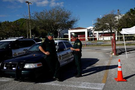 FILE PHOTO: Police officers Jamie Rubenstein (C) and Brad Griesinger talk as they stand guard in front of the Marjory Stoneman Douglas High School, after the police security perimeter was removed following a mass shooting, in Parkland, Florida, U.S., February 18, 2018. REUTERS/Carlos Garcia Rawlins/File Photo