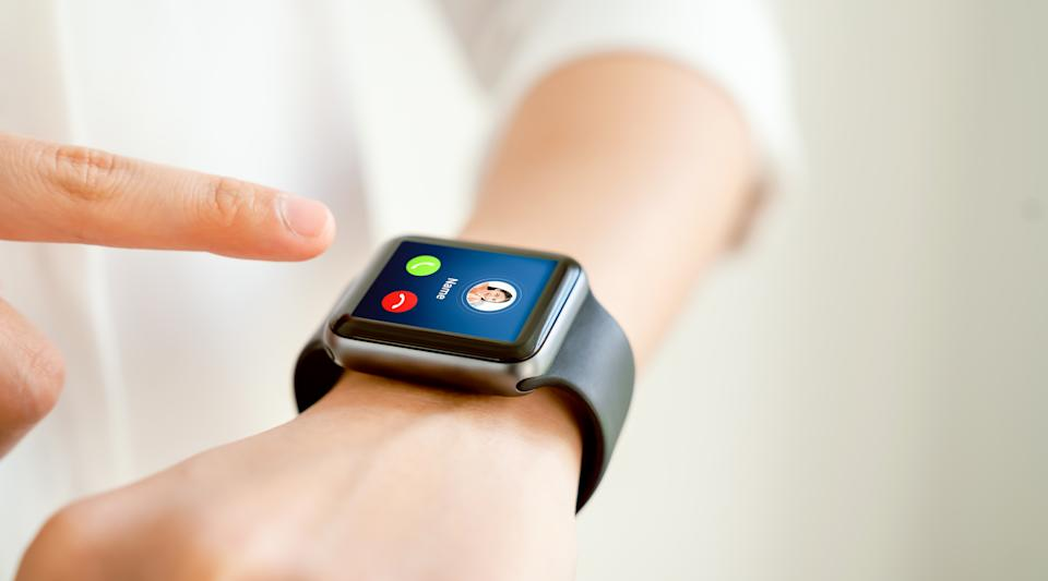 Woman hand touching on smartwatch to unlock and show call screen with friend.