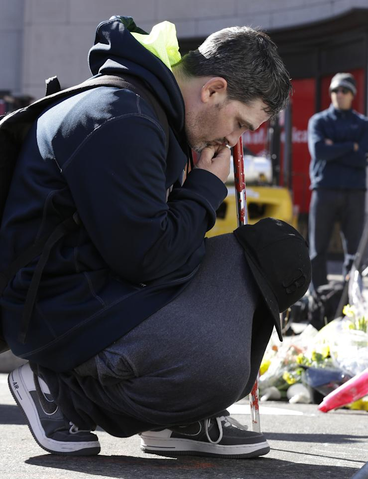 Robert Bakoian, 38, of Boston, reflects near a makeshift memorial on Boylston Street, Wednesday, April 17, 2013, in Boston. The city continues to cope following Monday's explosions near the finish line of the Boston Marathon. (AP Photo/Julio Cortez)