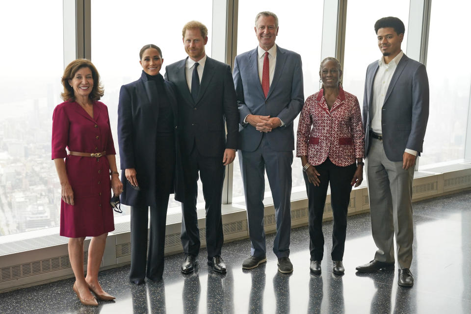 Meghan Markle, second from left, and Prince Harry, third from left, pose for pictures with New York governor Kathy Hochul, left, New York City mayor Bill de Blasio, third from right, first lady Chirlane McCray, second from right, and her son Dante de Blasio at the observatory in One World Trade in New York, Thursday, Sept. 23, 2021. (AP Photo/Seth Wenig)