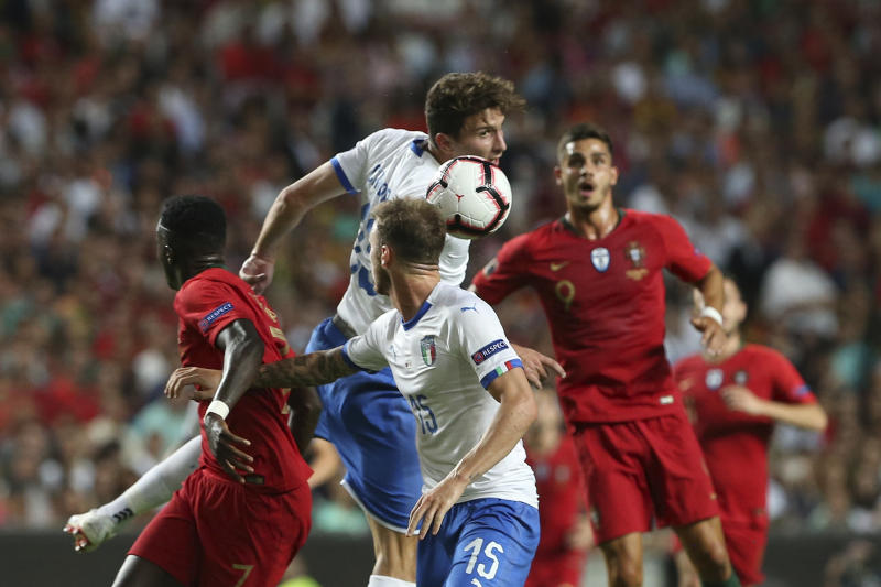 Italy's Mattia Caldara, centre, jumps for as header during the UEFA Nations League soccer match between Portugal and Italy at the Luz stadium in Lisbon, Monday, Sept. 10, 2018. (AP Photo/Armando Franca)