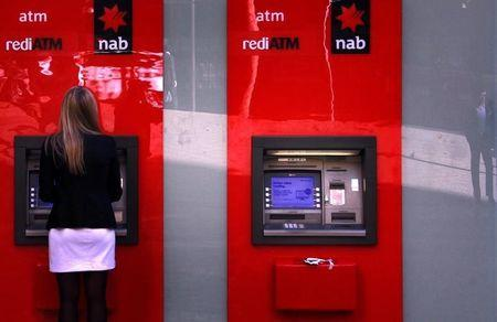 Man is reflected in glass panel next to a woman using National Australia Bank ATM in central Sydney