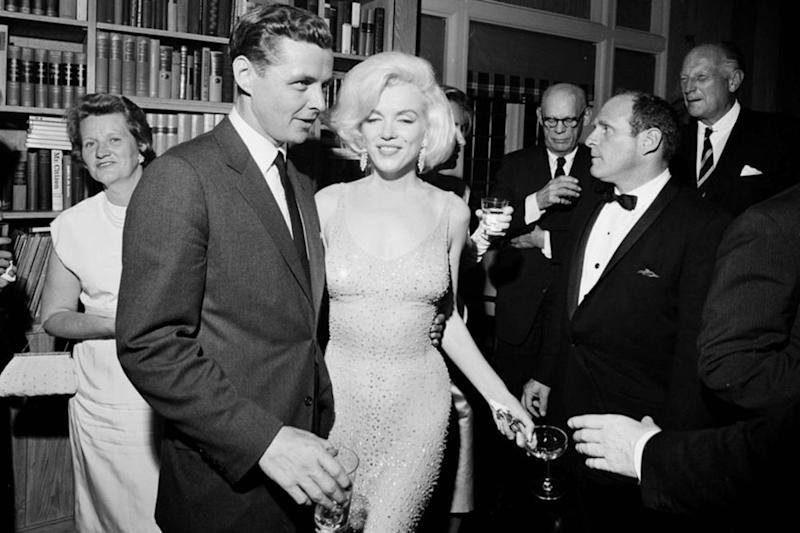 Marilyn Monroe (center), in the dress she wore to sing for President John F. Kennedy, pictured with President Kennedy's brother-in-law Steve Smith (left)