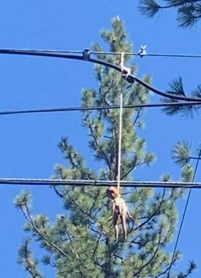 A disfigured Black doll hangs hanged on a noose suspended from a South Lake Tahoe power line on Tuesday.