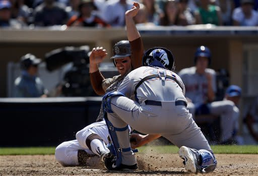 San Diego Padres' John Baker, left, beats the tag of New York Mets catcher Josh Thole while scoring on a double by Mark Kotsay during the eighth inning of a baseball game on Sunday, Aug. 5, 2012, in San Diego. (AP Photo/Lenny Ignelzi)