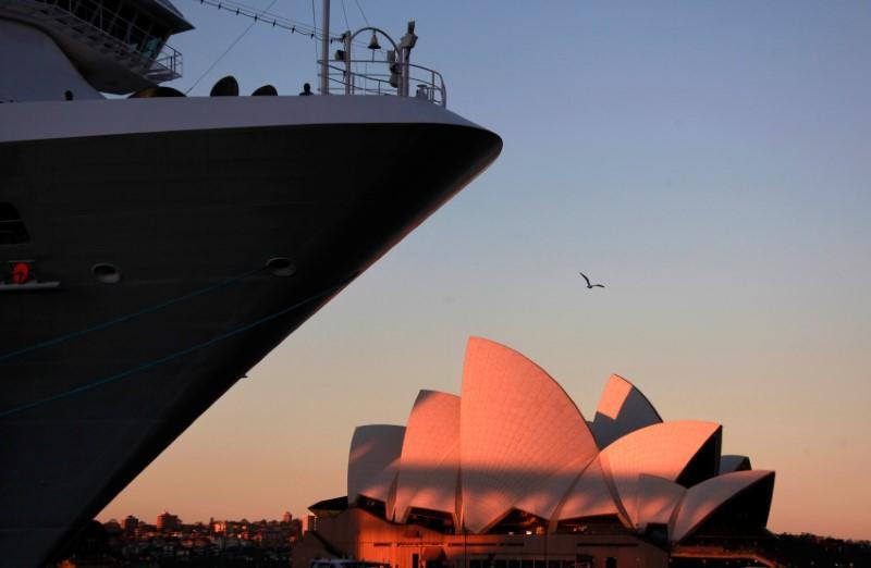 FILE PHOTO: A passenger stands aboard the Carnival Cruise Lines ship called the 'Carnival Spirit' as it sits docked opposite the Sydney Opera House