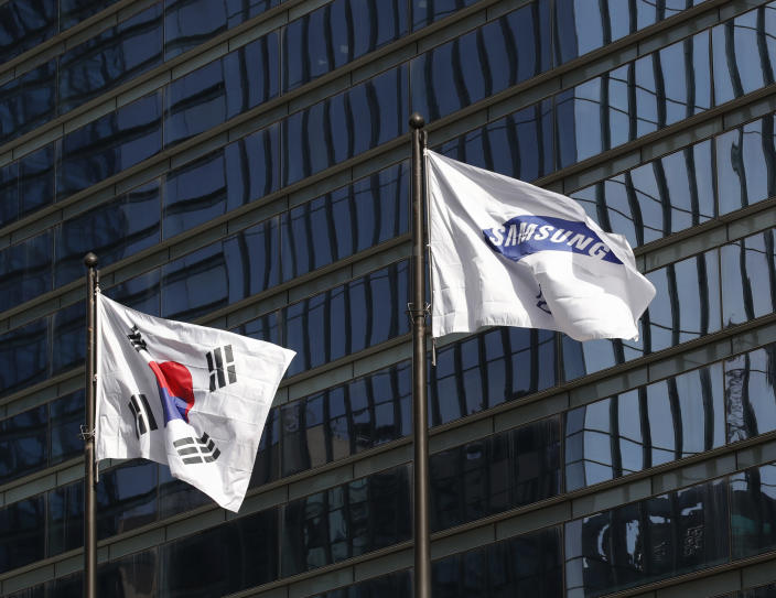 A flag of Samsung flutters next to the South Korean national flag outside of Samsung's Seocho office building in Seoul, South Korea, Sunday, Oct. 25, 2020. Lee Kun-Hee, the ailing Samsung Electronics chairman who transformed the small television maker into a global giant of consumer electronics, has died, a Samsung statement said Sunday. He was 78. (AP Photo/Lee Jin-man)